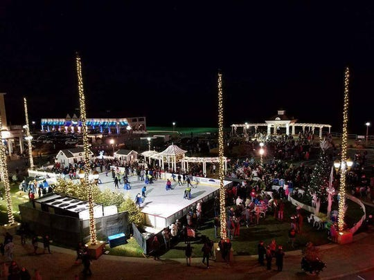 The outdoor ice rink in Pier Village at night.