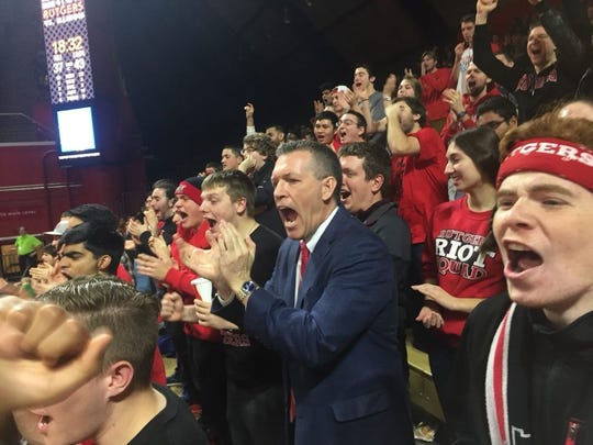 Rutgers athletics director Pat Hobbs (center, in suit)