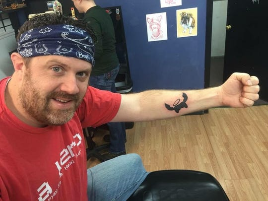 Jeromy Adams, who created video game fundraiser Extra Life, shows off his tattoo of the Extra Life logo.