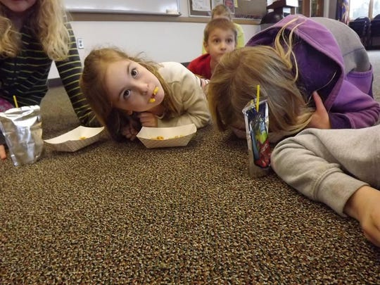 Youngsters get to eat their snacks kitty style after finishing a book about cats