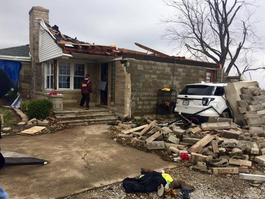 Friends and family of Jenna and Zach Meyer help clear out the tornado-damaged home Wednesday. The roof was torn off the home during the storm Tuesday.