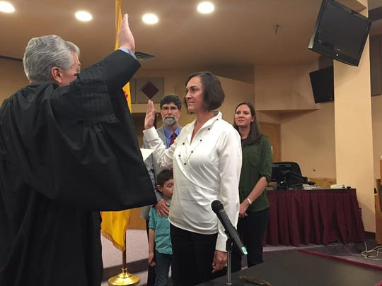 Terrie Dallman takes the oath for Las Cruces school board, administered by District Judge Fernando Macias, as her family looks on.
