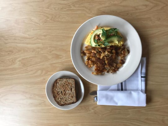 The shrimp omelet is topped with fresh avocado; it's shown here served with Mimosa potatoes, browned in olive oil.