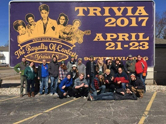 Staff from WWSP 90FM sits in front of a billboard for this year's Trivia contest on Division St.