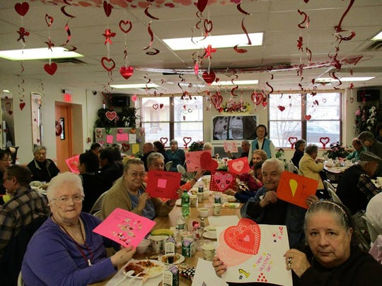Seniors at Southwest Senior Activity Center show off the valentines that young volunteers made in February.
