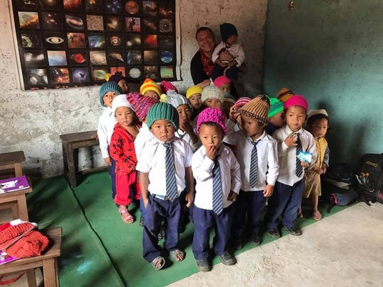Terry Mikeska visits with young students in Nepal, presenting them with homemade hats from San Angelo.