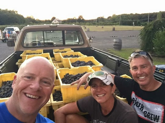 Tim and Jackie Schlitzer  caretakers/managers ,and Jerry Amabile, owner of Cream Ridge Winery, pose with fruits of their vineyard.