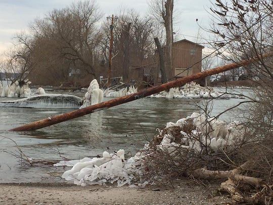 Utility pole in the gap opened up by waves and wind in the spit of land separating Sodus Bay and Lake Ontario.