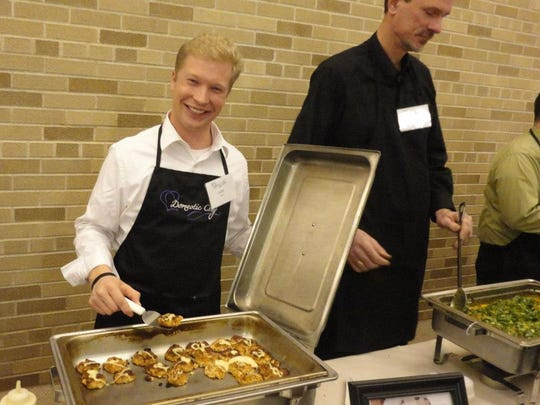 Manitowoc Mayor Justin Nickels (left) serves a dish at Domestic Chef, a fundraiser for Manitowoc County's Domestic Violence Center.