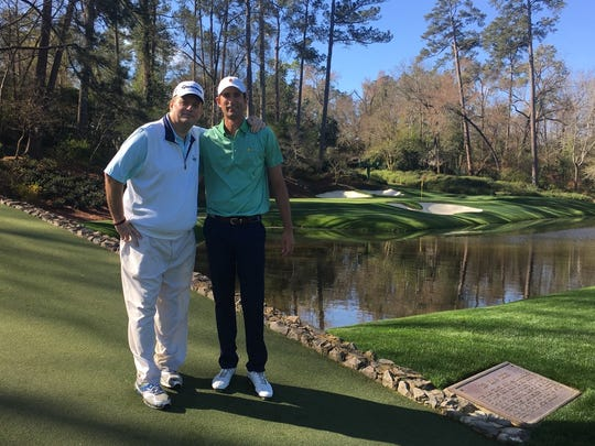Red Bank caddie John Doherty (left) and golfer Stewart Hagestad stand on the Hogan Bridge at Augusta National during a practice round in February.