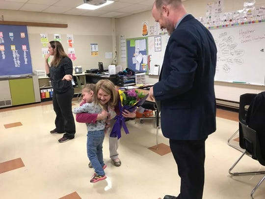 Teacher consultant Pam Patterson hugs one of her students after being named the Advocator of the Year by Superintendent Jamie Cain on Thursday, May 4.