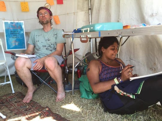 """Joe Kane and Mythili Sanikommu work on poems as part of """"Poetry on Demand"""" at Bonnaroo in 2016. The concept, which turns short stories or anecdotes from passers by into poetry in just minutes, is an initiative of the Nashville writer's collective called The Porch. It will return to Bonnaroo this year, but with a twist - stories are now being recorded for potential inclusion in the soon-to-be-launched national podcast called Versify."""