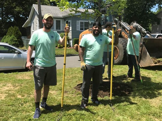 Volunteers from the Anheuser Busch brewery in Newark beautify a park along the Passaic River in Little Falls.