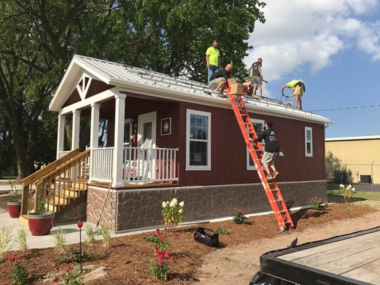 A crew installs solar panels on a tiny home at Eden