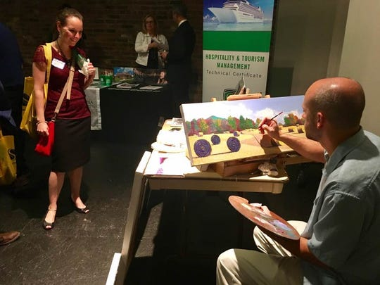 Artist Kyle Coffman paints while featuring his work at the Business & Education Expo at The Factory at Franklin on June 20, 2017.