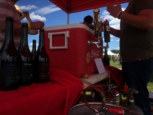 A cooler of Angry Orchard cider sits out on a table as patrons try samples. Angry Orchard opened its Walden facility in 2015.