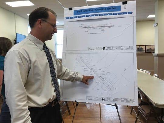 Jonathan Pera, principal engineer for a project to construct a footbridge in the Morris Canal Greenway, looks at drawings for the proposed bridge.