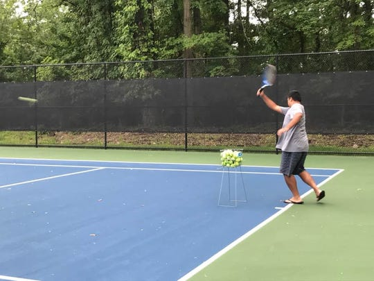 Omar Santos practices his serves at the new tennis court thatrecently opened to the public.