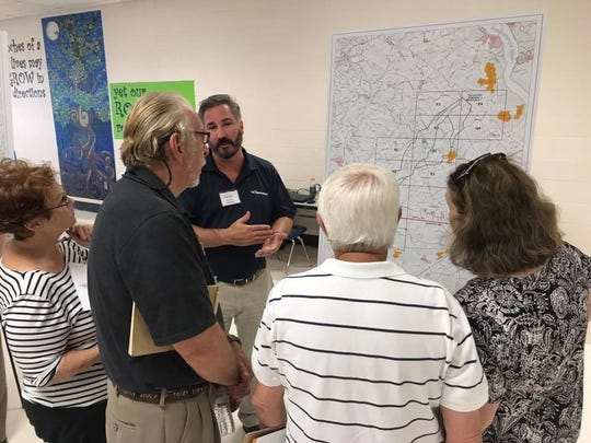A Transource Energy employee explains a preliminary power line map presented to landowners at an open house. Jana Benscoter/photo