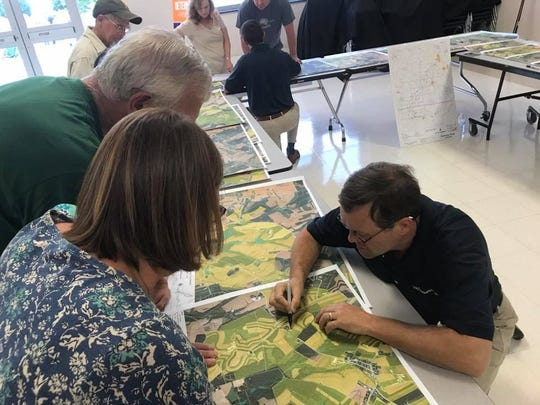 Landowners ask questions about their property, and how it will be affected by a preliminary proposal of an above-ground power line. Jana Benscoter/photo
