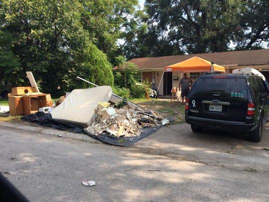 Lina Hernandez's belongings are piled outside her flood-damaged