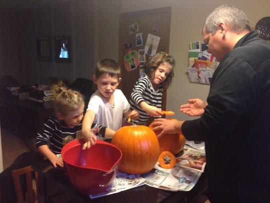 The Braatz family digs out pumpkin guts.