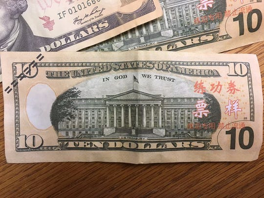 The counterfeit bills have three lines of red simplified