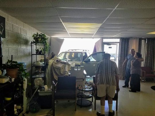 Twisted Scissor employees and clients stand back and observe the vehicle that just crashed through the salon's window Friday.