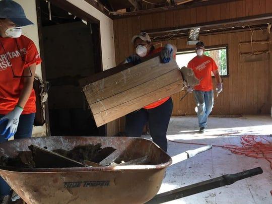 Volunteers strip a flood-damaged Texas home.
