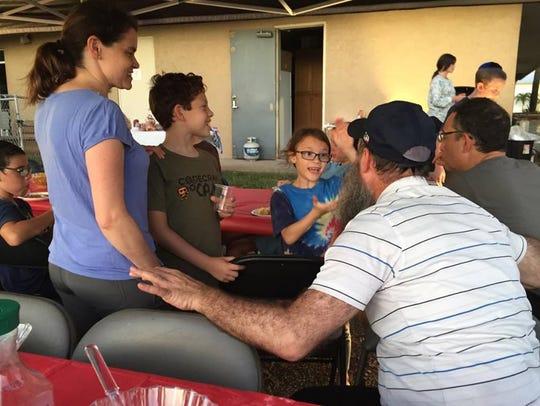 Rabbi Zvi Konikov talks with several children during