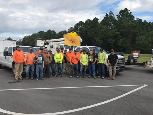 A crew of linemen from New Mexico lead by Joseph Bizzell proudly display the New Mexico flag before Hurricane Irma took landfall.