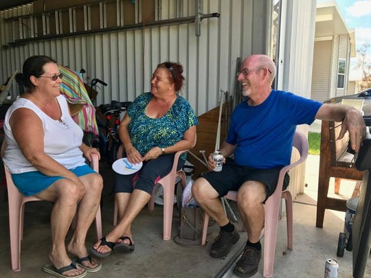 Debbie Love (left) chats with her neighbors Donna and Kevin Pugh in their garage in West Wind Estates in East Naples on Sept. 16, 2017. The senior community was hit by Hurricane Irma on Sept. 10, 2017.