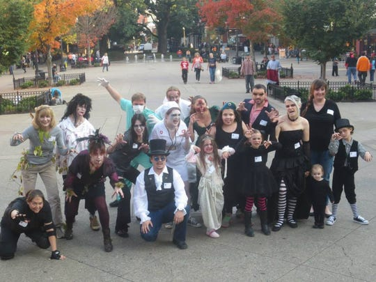 """Zombie dancers celebrate completing the choreographed dance from the video for Michael Jackson's """"Thriller."""""""