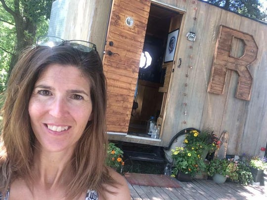 Renee McLaughlin, organizer of TinyFest Midwest from Oskaloosa, lives in an 87-square-feet dwelling, pictured behind her.