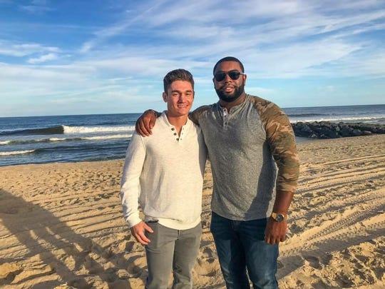 Dustin Fleischer, left, with rescuer Edrick Alleyne at Seven Presidents Beach.