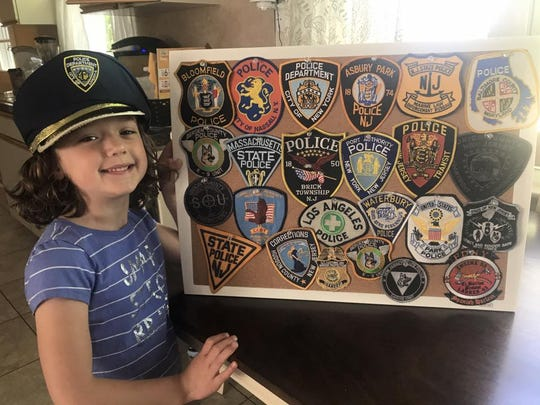 Morgan Blann shows off her growing collection of police department patches.