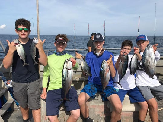 A group on the Paramount party boat hold up their catch of bonito and false albacore.