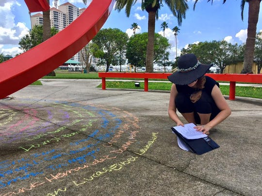 Sarah Brown, a senior at Fort Myers High School, spent Saturday writing the names of victims of mass shootings at Centennial Park in downtown Fort Myers.