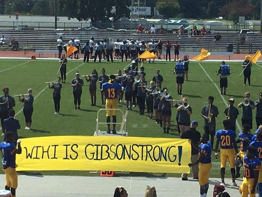 The Wi-Hi football team displays a banner for Glenn