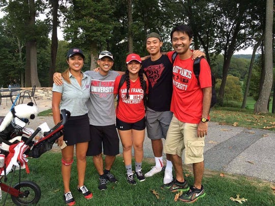 Desiree Razon, left, with her family who are repping Saint Francis University paraphernalia.