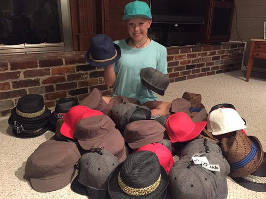 Hannah Grubbs sorts through a pile of hats.
