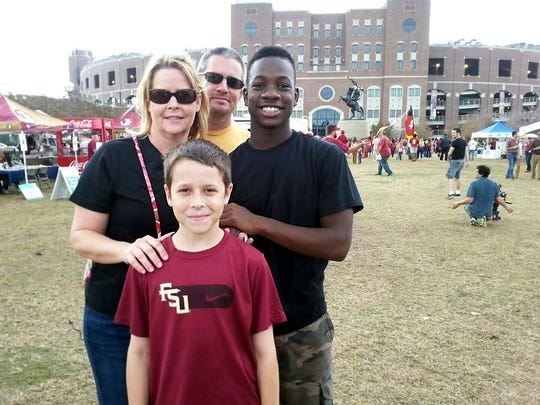 JaJuan Cherry (right) poses with his family (left to right) Dana Tedders, Deven Tedders, and Dylan Tedders in front of Florida State University's Doak Campbell Stadium in Tallahassee.