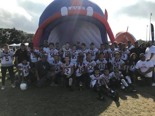 The Las Cruces Rough Riders youth football team celebrates a third-place win Friday, Dec. 8, 2017, in the American Youth Football league's national championship tournament in Florida.