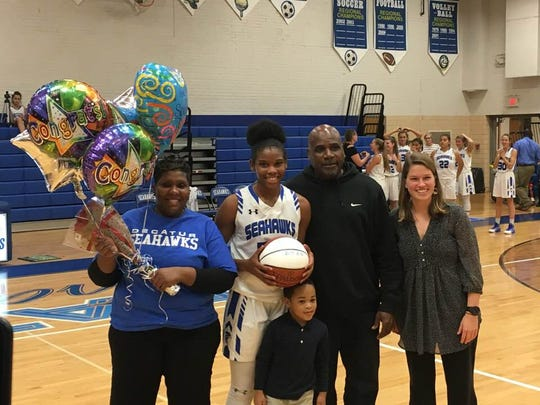 Amya Mumford stands with her parents and Coach Kate Coates after scoring her 1,000th career point on Dec. 7, 2017.