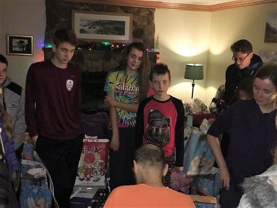 Aidan, Shannon, and Liam watch their dad, Patrick Seaver, open a gift from Mojo in the Morning radio show.