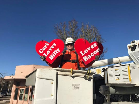 Pacific Power lineman Van Schoenborn prepares to hang Walk of Hearts messages last February in downtown Stayton