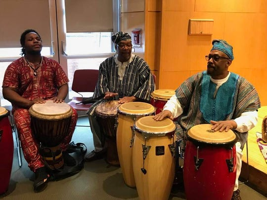 Kzurii Zahiratu, Kofi Mahama and Billy Bungo, from left, play the drums during the Kwanzaa celebration at the Montclair Public Library on Dec. 17, 2017.