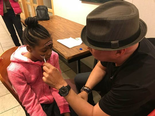 Angel Rae Hankerson, 11, gets her face painted during