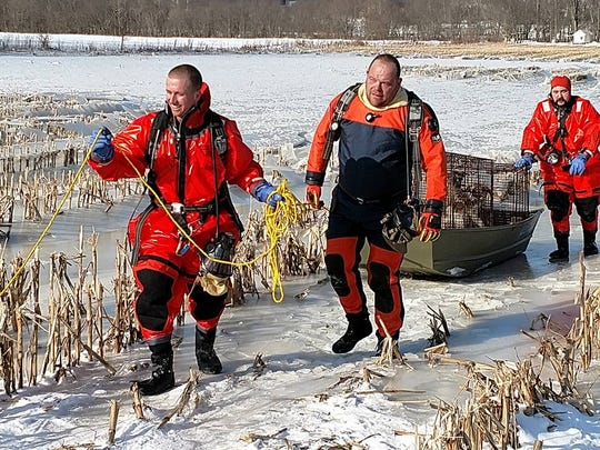 Assistant Dog Warden Ryan Conkle, Captain Dave Stone and Aaron Beaver of the Walhonding Valley Fire District rescue four dogs from a campground that suffered flooding over the weekend along the Walhonding River outside Warsaw.