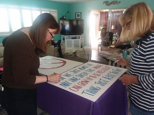 Space Coast residents craft signs for the Jan. 20 Brevard